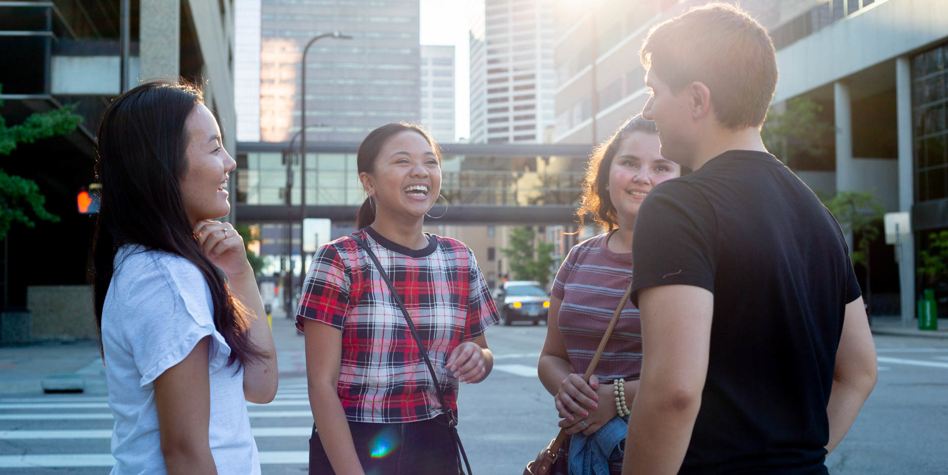 Group of students talking to each other on a sidewalk in downtown Minneapolis