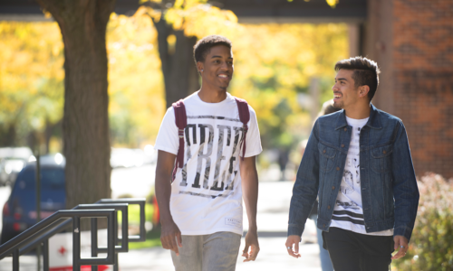 Two students walking next to each other outside in autumn.