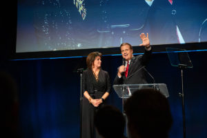 President Scott Hagan and his wife Karen speaking on stage wearing dark formal clothing in front of a projector screen.